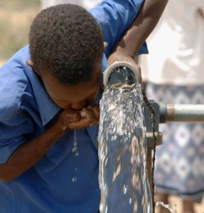 African boy drinking from well in Kenya