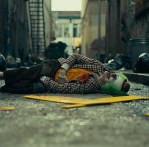 Arthur Fleck gets beat up as a clown the Joker movie Joaquin Phoenix